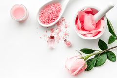 Make cosmetics with rose oil. Mortar with rose petals and pestle on white background top view copyspace. Make cosmetics with rose oil. Mortar with rose petals royalty free stock image