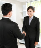 Make a deal. Hand shake between a businessman and a businesswoman in office environment Royalty Free Stock Photo