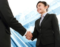 Make a deal. Hand shake between a businessman and a businesswoman in office environment Royalty Free Stock Images