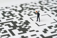 Make a decision for solution for business idea concept, miniatur. E figure businessman standing at the center of confusing QR code labyrinth maze thinking to royalty free stock photo