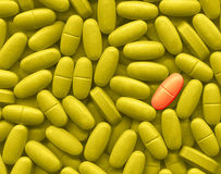 Make the difference. A lot of yellow pills and one red Royalty Free Stock Photos