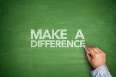 Make a difference on blackboard. Make a difference on green blackboard with hand Stock Photo