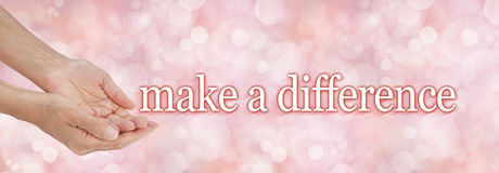 Make a difference charity campaign background. Female hands cupped gesturing for donations with the words MAKE A DIFFERENCE floating away on a light pink bokeh stock photo