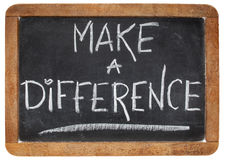 Make a difference. Motivational phrase - white chalk handwriting on a vintage slate blackboard Stock Photos