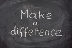 Make a difference phrase on blackboard. Make a difference motivational phrase handwritten with white chalk on blackboard Stock Photo