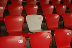 Make a difference. Raws of chairs in red colour to the exception of a different coloured one Stock Photo