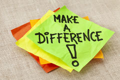 Make a difference reminder. Make a difference -motivational reminder on green sticky note against canvas board Royalty Free Stock Photo