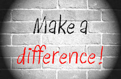Make a difference. Text written in black and red on a black and white brick wall with vignetting Royalty Free Stock Photography
