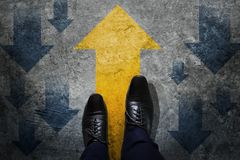 Make the Different and Leadership Concept, Businessman with Black Oxford Shoes Walking with Opposite Arrow Direction from. Other, Top View, Dark Cement Grunge stock photo