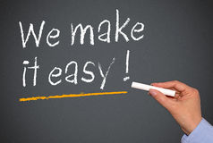 We make it easy !. Blackboard with white chalk text message saying ' We make it easy !' underlined in yellow Royalty Free Stock Image