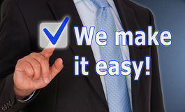 We make it easy business concept. Finger of businessman pressing we make it easy button with check mark on interactive screen stock photography