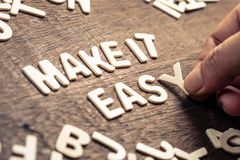 MAKE IT EASY. Closeup hand place the wood letters on wood table as the phrase MAKE IT EASY stock image