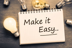 Make It Easy. Concept, handwriting on notebook with light bulbs Royalty Free Stock Photos