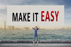 Make it easy. We make it easy, words on blank board hold by a young girl in the outdoor Stock Photo