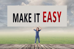 Make it easy. We make it easy, words on blank board hold by a young girl in the outdoor Royalty Free Stock Photo