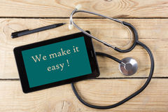 We make it easy! - Workplace of a doctor. Tablet, medical stethoscope, black pen on wooden desk background. Top view. We make it easy!  - Workplace of a doctor Royalty Free Stock Photography