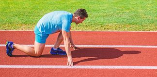 Make effort for victory. Adult runner prepare race at stadium. How to start running. Sport motivation concept. Man. Athlete runner stand low start position royalty free stock photography