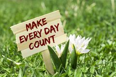 Make every day count. On wooden sign in garden with white spring flower Stock Photography