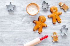 Make gingerbread cookie for new year 2018. Gingerbread man, rolling pin, flour on grey wooden background top view.  stock images