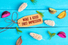 Make a good first impression text on paper tag. With rope and color dried flowers around on blue wooden background royalty free stock photography