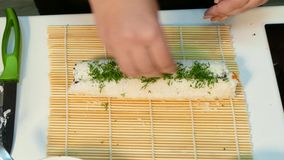 Wrap sushi and sprinkle with herbs stock video footage