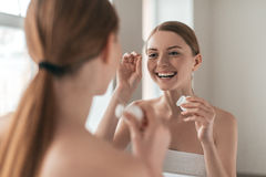 Make it a habit. Over the shoulder view of young beautiful woman holding dental floss and smiling while looking in the mirror Stock Image