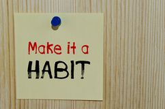 Make it a habit written on paper note Stock Photo