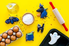Make halloween gingerbread concept. Icing cookies near rolling pin, baking sheet, eggs, flour on yellow background top stock photography