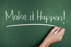 Make it happen. Woman hand writing Make it happen note on green blackboard stock photo