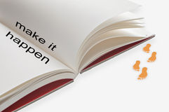 Make it happen word with footstep. On book on white background Stock Image