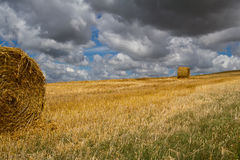 Make Hay While The Sunshines!. A golden landscape of rolling fields is punctuated with two large round bales of harvested straw. Dark clouds and deep blue skies Royalty Free Stock Image
