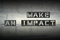 Make an impact gr. Make an impact stencil print on the grunge white brick wall Stock Photography