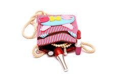 Make kit lipstick nail polish coming out of girl handy bag Stock Images