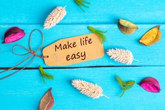 Make life easy text on paper tag. With rope and color dried flowers around on blue wooden background stock images