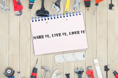 Make it, live it, love it against tools and notepad on wooden background Royalty Free Stock Photos