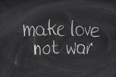 Make love not war on blackboard Stock Photos