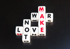 Make love not war. Text ' make love not war ' inscribed in uppercase letters on small white cubes arranged crossword style , black background Stock Photography