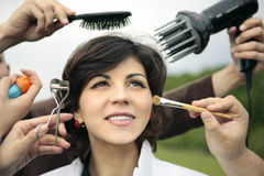 Make me beautiful. Happy smiling lady surrounded by a lot of hands that are working at her face and hair Stock Photos