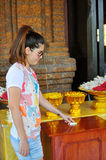 Make merit. Thai girl make merit by put the money into the donate box, Thai temple Royalty Free Stock Photography