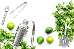 Make mojito cocktail with lime and peppermint in shaker. White background top view copyspace stock image