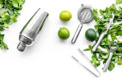 Make mojito cocktail with lime and peppermint in shaker. White background top view copyspace. Make mojito cocktail with lime and peppermint in shaker. White royalty free stock photo