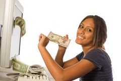 Make money from the Internet. A girl pulling dollar bills from the computer. Making money from the internet and the computer. Looking at the camera smiling royalty free stock image