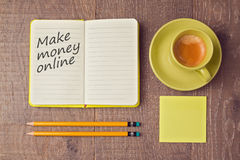 Make money online concept with notebook and coffee cup. View from above Royalty Free Stock Photo