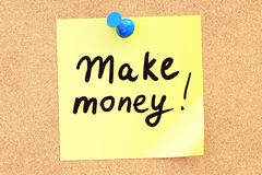 Make money! Text on a sticky note pinned to a corkboard. 3D rend Stock Photos