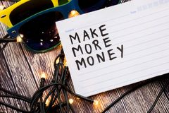 Make more money handwritten on a registers page with black color. Two sunglasses in various combinations of colors with lights set. Make more money handwritten royalty free stock image