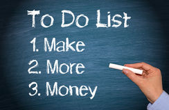 Make more money to do list. Hand of a woman writing a make more money to do list on a blackboard Stock Images