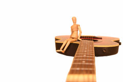 Make music. Doll sitting on a red guitar royalty free stock photo