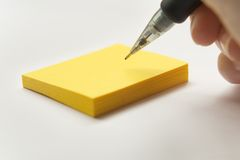 Make a Note. A pencil is poised over a yellow sticky note pad, prepared to write. Isolated on white background Royalty Free Stock Photos