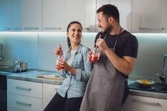 Make och fru som har gyckel med smoothien i köket royaltyfri foto