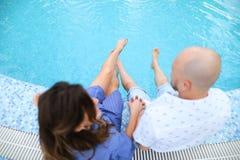 Make och fru som sitter den barfota near simbassängen fotografering för bildbyråer